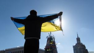 A protester raising a Ukrainian flag. Photo: Neil Spicer