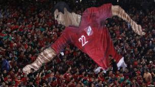 Al Ahly fans hold up a 3D figure of footballer Mohamed Abo Trika at the Cairo International Football Stadium, Egypt - Thursday 20 February 2014