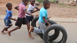 Children play with tyres on a street in Katlehong township, South Africa - Friday 14 February 2014