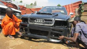 Godfrey Namunye and a work mate working on a car at his workshop in Kampala, Uganda