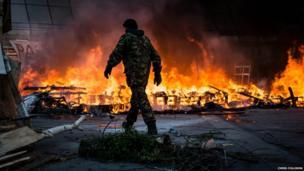 A man walks past a wall of fire. Photo: Chris Collison