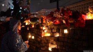Mourners light candles at vigil. Photo: Maximilian Clarke