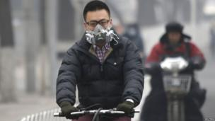 A man wearing a mask rides a bicycle in Beijing 24 February 2014