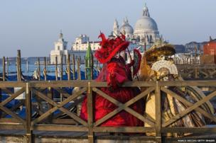 Two women dressed in Carnival Costumes pose in Saint Mark's Square in Venice, Italy