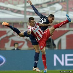 Manchester United's defender Chris Smalling (right) jumps for the ball with Olympiakos midfielder Hernan Perez