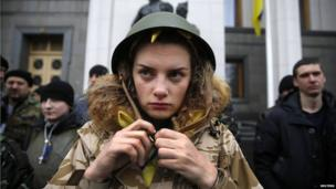 An anti-Yanukovich activist buckles her helmet as she stands guard outside the parliament building in Kiev