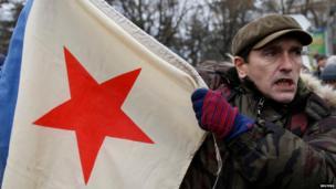 Man holds Soviet-era Russian flag in Simferopol, Crimea (28 Feb)