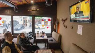 Kiev residents watch Yanukovych news conference in cafe (28 Feb)