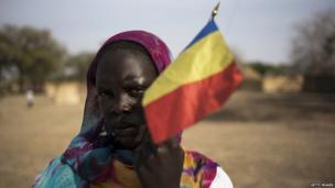 A Chadian woman carries her national flag