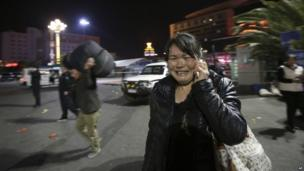 A woman reacts at the crime scene outside Kunming railway station on Saturday 1 March 2014
