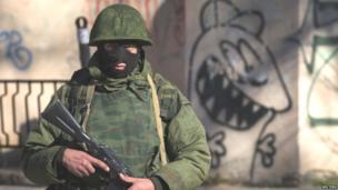 An armed man stands near a Ukrainian military base in Simferopol, Crimea