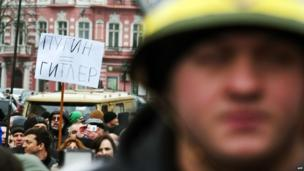 """A demonstrator holds a placard reading """"Putin=Hitler"""" as people take part in an anti-war rally in the Ukrainian Black Sea city of Odessa"""