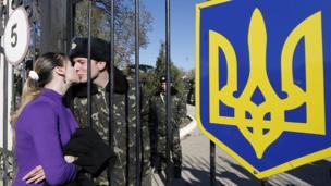 Ukrainian serviceman kisses through gate
