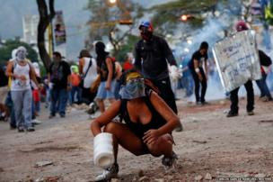 Anti-government protesters clash with riot police during a protest against Nicolas Maduro's government in Caracas
