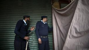 Police officers peek through a curtain at the site of a twin suicide bombing in a court complex in Islamabad, Pakistan