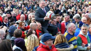 Shrovetide ball being carried through Ashbourne by local businessman Stuart Lees
