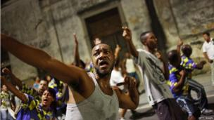 Revellers celebrate during a pre-Carnival march of the Unidos da Tijuca samba school through the historic Afro-Brazilian port district on 20 February 2014 in Rio de Janeiro