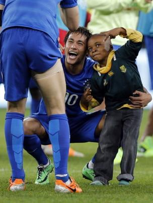 Footballer Neymar poses for a photographer with a young pitch-invader