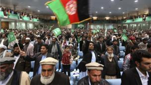 Supporters of Afghan presidential candidate Abdul Rassoul Sayyaf stand for the National Anthem during an election gathering in Kabul
