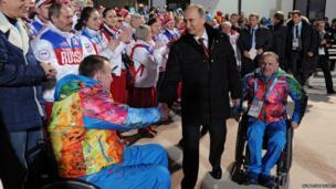Vladimir Putin shakes hands with athletes