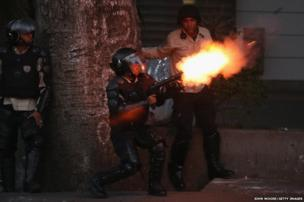 Venezuelan national police fire tear gas at anti-government protesters in Caracas, Venezuela