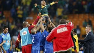 A South African boy is carried by Brazil's players at the end of a friendly match between South Africa and Brazil at Soccer City stadium in Soweto