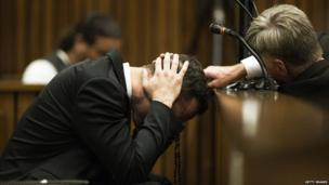 A member of Oscar Pistorius' legal team reaches out to him during the fourth day of his trial