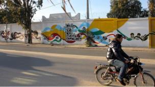 A man rides past Tunisia's longest street mural i in Kasserine