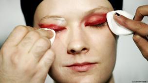 A model gets her eye make-up removed