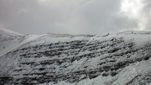 Mick Lloyd striding ahead toward the Tommy Jones obelisk on Pen-y-Fan on the Brecon Beacons on St David's Day