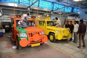 Indian workers give the final touches to election campaign vehicles bearing BJP and and Telugu Desam party (TDP) symbols and logos in Hyderabad.