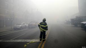 A firefighter cordons off the street at the scene of the incident