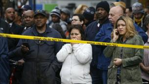Shocked residents try to contact friends and relatives across the street from the building