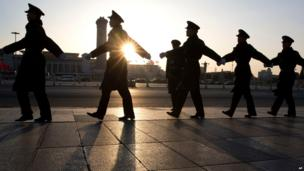 Soldiers march outside the Great Hall of the People before the closing ceremony of the National People's Congress in Beijing, China