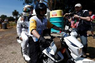 Mercedes Formula One driver Lewis Hamilton of Britain (in white) is taken back to the pits during the first practice session of the Australian F1 Grand Prix at the Albert Park circuit in Melbourne.