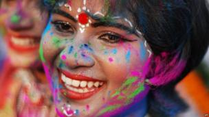 An Indian child adorned with coloured powder takes part in celebrations for the spring festival Holi in Bhubaneswar on 16 March 2014