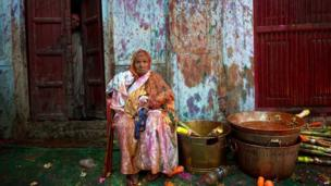 An Indian widow rests celebrating Holi with water and gulal (coloured powder) in Vrindavan on 14 March 2014