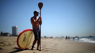 A paddle-boarder looks out at the Pacific Ocean in Santa Monica, California