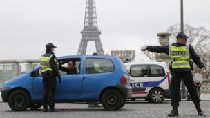 Police officers in front of the Eiffel Tower, in Paris