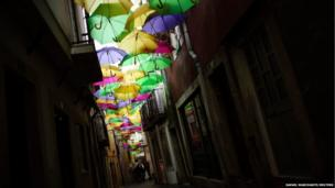 A street is seen decorated with umbrellas of different colours