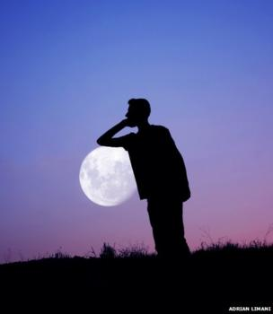 The silhouette of a man against the backdrop of the full moon in a purple sky. He appears to be leaning on the Moon.