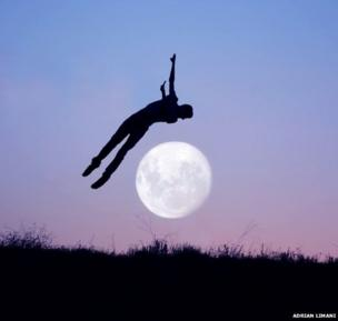 The silhouette of a man against the backdrop of the full moon in a purple sky. The man appears to be jumping over the moon.