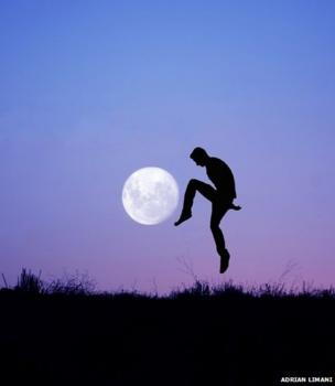 The silhouette of a man against the backdrop of the full moon in a purple sky. He appears to be playing football with the Moon.