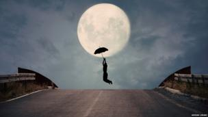 The silhouette of a man holding an umbrella against the backdrop of a large full moon. The man appears to be flying, like Mary Poppins.