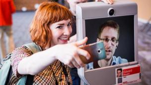 Woman with Edward Snowden on a screen