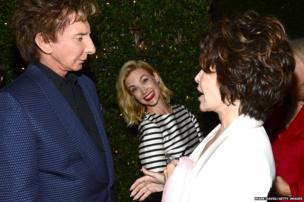 Singer Barry Manilow talks to Carole Bayer Sager as actress January Jones smiles at the photographer