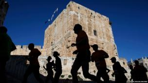 Athletes are silhouetted as they participate in the fourth international Jerusalem marathon
