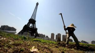 A farmer tills the field near a replica of the Eiffel Tower