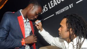 Former French international football star Christian Karembeu signs a fan's jacket in Lagos, Nigeria - Saturday 15 March 2014