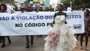 A woman in a blood-stained wedding dress takes part in a protest about Mozambique's rape laws - Thursday 20 March 2014